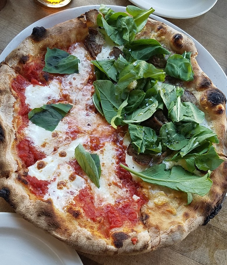 On the left Margherita (tomato sauce, fresh mozzarella, and basil); on the right Biancoverde (fresh mozzarella, parmigiano reggiano, ricotta, and arugula) with fennel sausage.